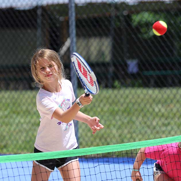 Girl playing tennis at Sports Camp.