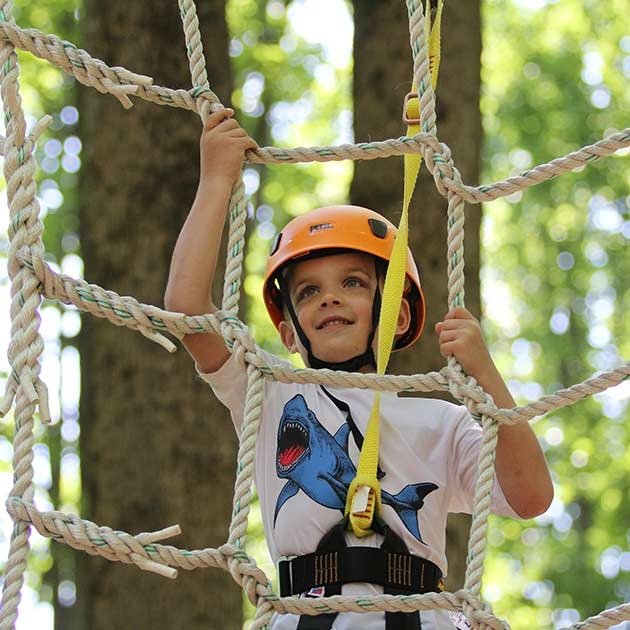 Boy climbing a rope ladder at our Jewish summer camp.