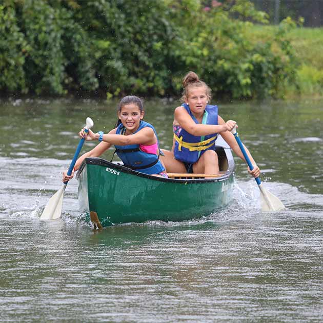 Two 7th grade girls canoeing at BT Camps in Baltimore County.