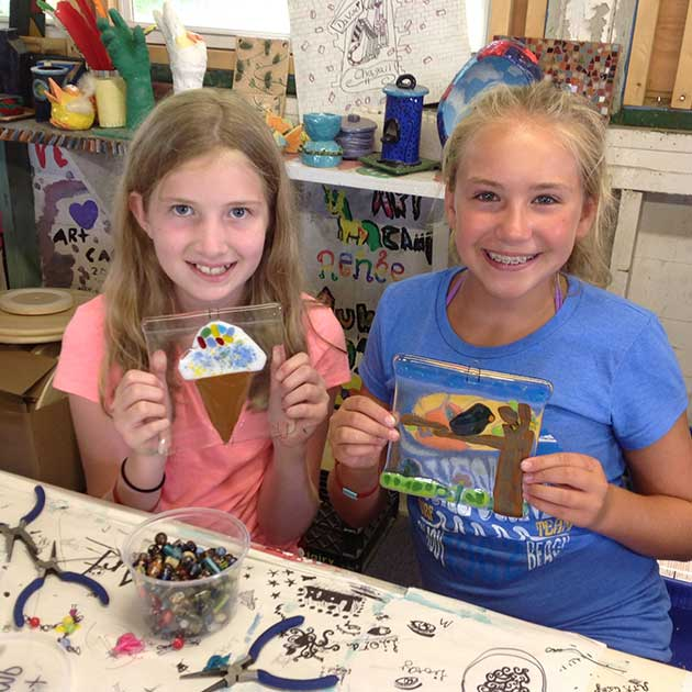 Two girls show off their projects at BT Camp's Art Summer Camp.