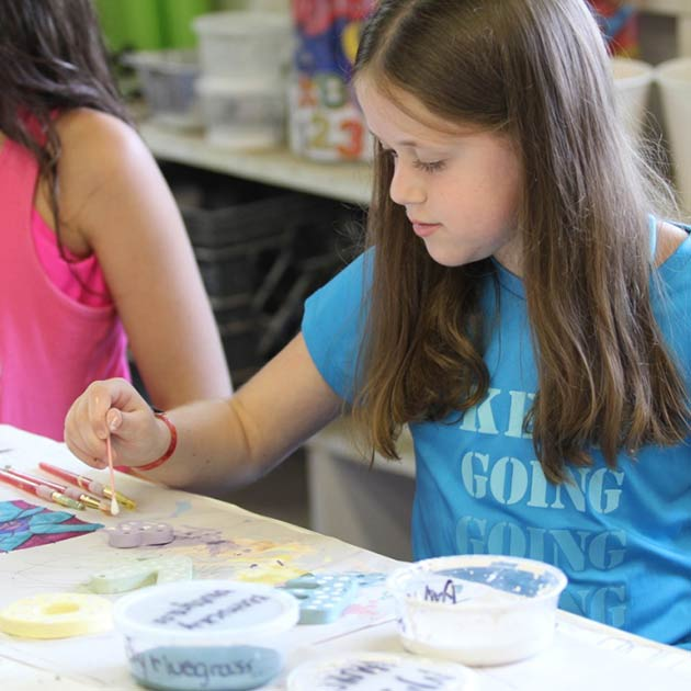 Young girl enjoys painting at Art Camp at BT Camps.