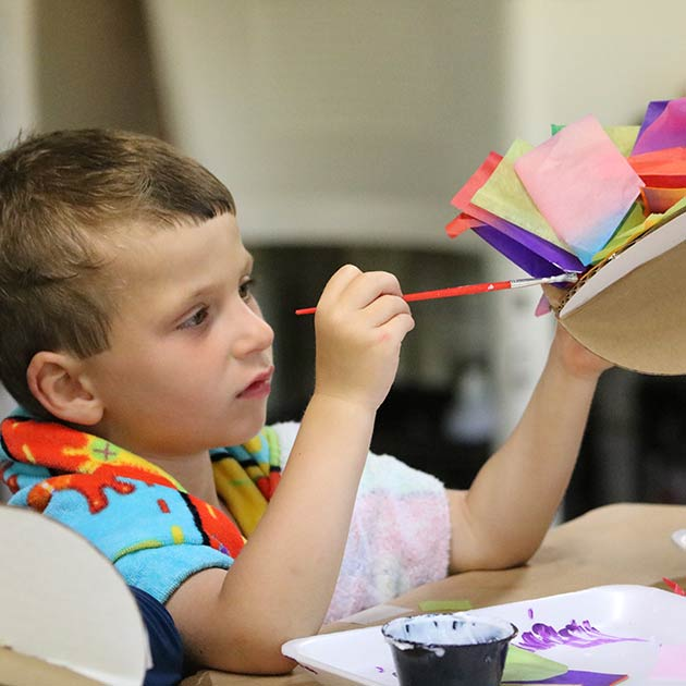 Small boy working hard on painting a craft..