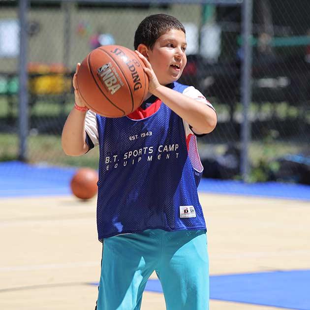 Boy throwing basketball at camp.