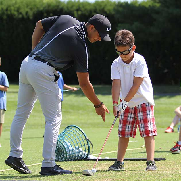 Instructor teaching boy how to play golf at camp.