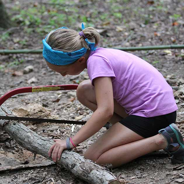 Girl learning outdoor skills at survival camp.