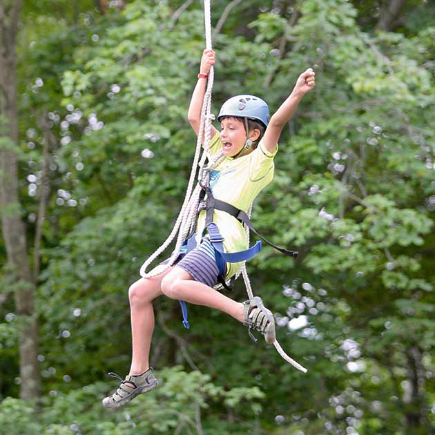 Boy rope swinging at Survival Camp.