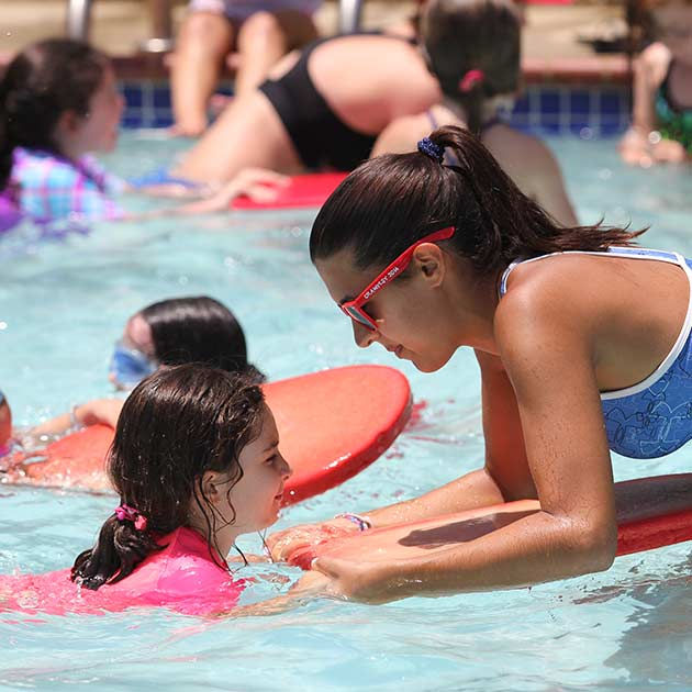 Instructor teaching girl to swim at summer camp.
