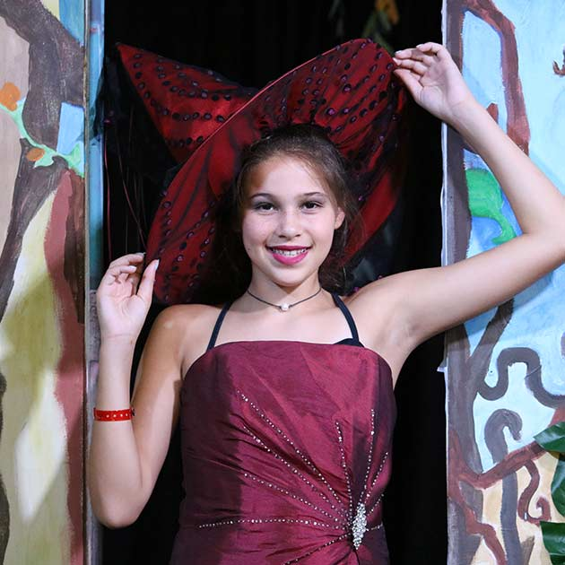 Girl posing during a play at Theatre Camp.
